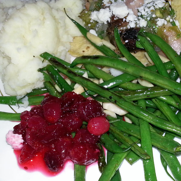 Thanksgiving plate with mashed potatoes, haricot vert, cranberry sauce and smoked turkey