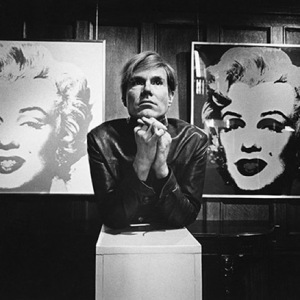 Andy Warhol in front of two paintings from his Marilyn series. Photograph by Donald Getsug